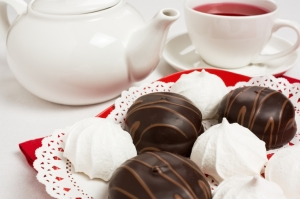 Delicious chocolate and meringue cake on red plate with tea cup and teapot