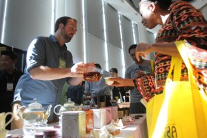 Alexander Harney of the Marketing Department, Harney and Sons, pours a sample for an attendee.